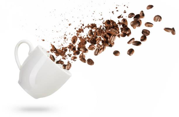 kaffeebohnen aus einer tasse verschüttet - kaffeepulver stock-fotos und bilder