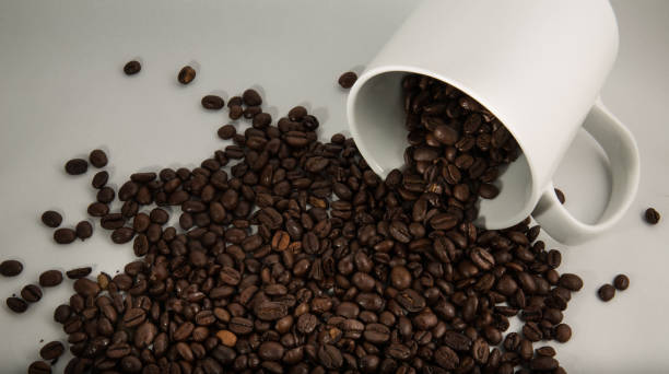 Coffee Beans Spilling From a Mug stock photo