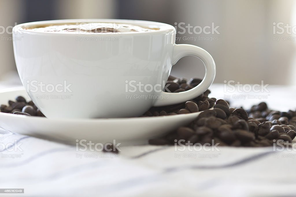 coffee beans with a Cappuccino cup royalty-free stock photo