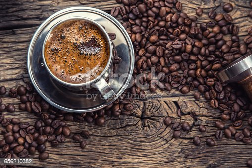 istock Coffee. Black coffee with coffee beans and portafilteron old oak wooden table. 656210382