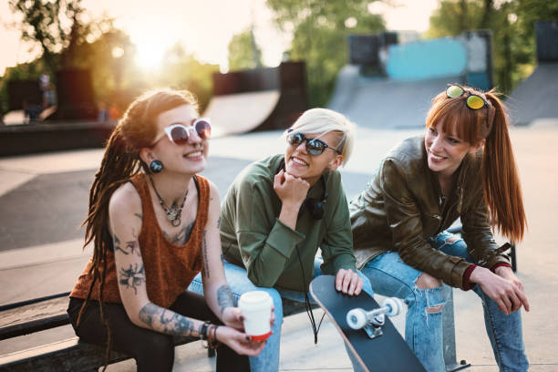 Coffee break and chat with friends in skate park stock photo