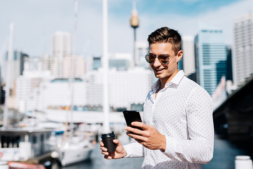 Portrait of handsome young Australian man with light brown hair and blue eyes. Businessman going for a coffee break to yacht club