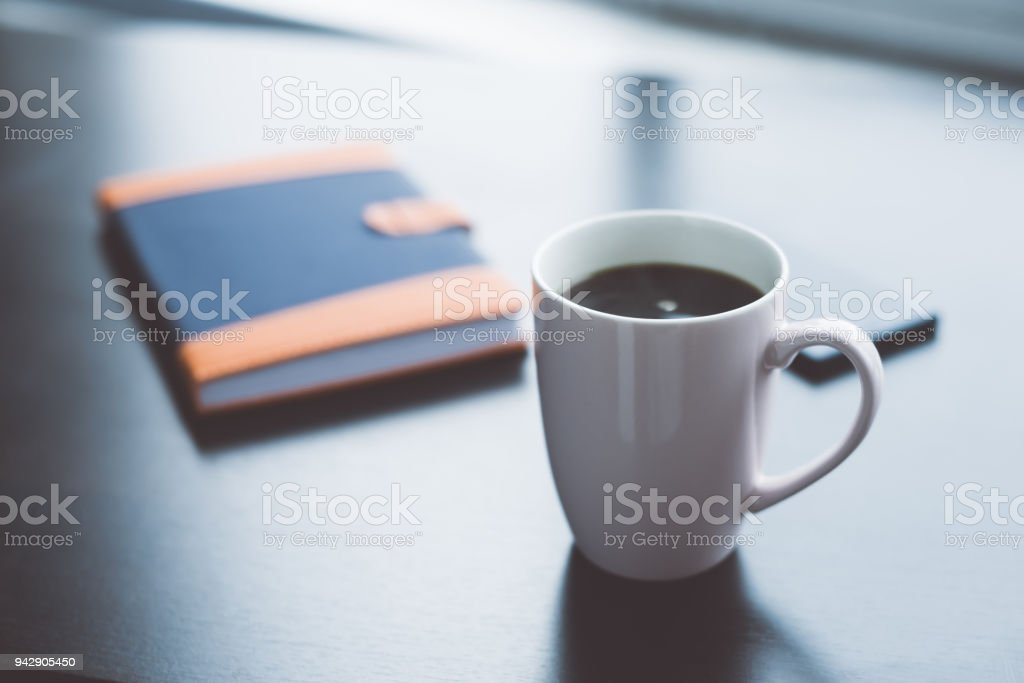 Coffee break business. Cup of coffee mobile phone and notebook. Morning coffee concept stock photo