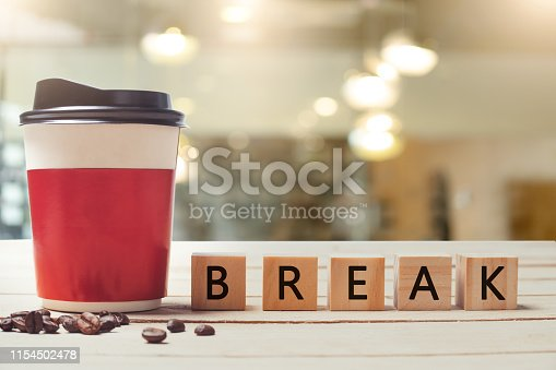 Coffee break concept. Paper coffee cup and wood letter with blurred coffee shop background.