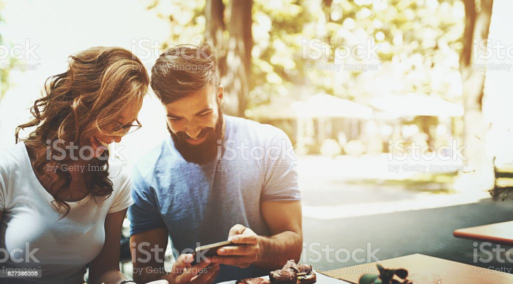 Coffee break conversation. Closeup front view of mid 20's couple having a coffee and a snack at a sidewalk cafe and looking at some social media news on his smartphone. It's sunny summer day, toned image. 20-29 Years Stock Photo