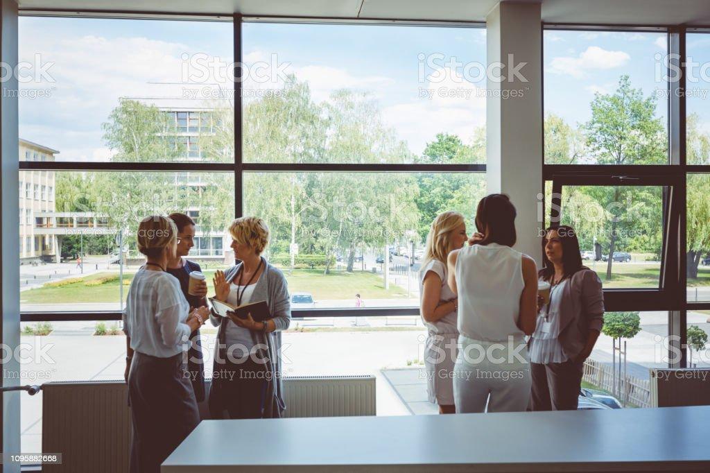 Coffee break during a seminar for woman Coffee break during a seminar for women. Group of women discussing during coffee break in seminar hall. Adult Stock Photo