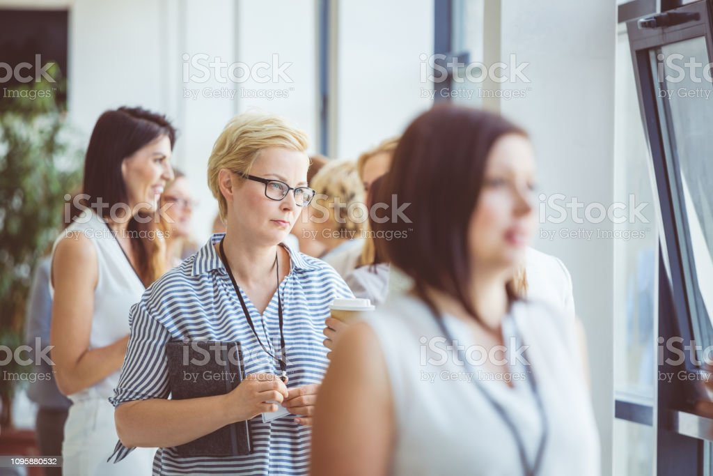 Coffee break during a seminar Group of women discussing during a break in conference hall. Coffee break during a seminar. Adult Stock Photo