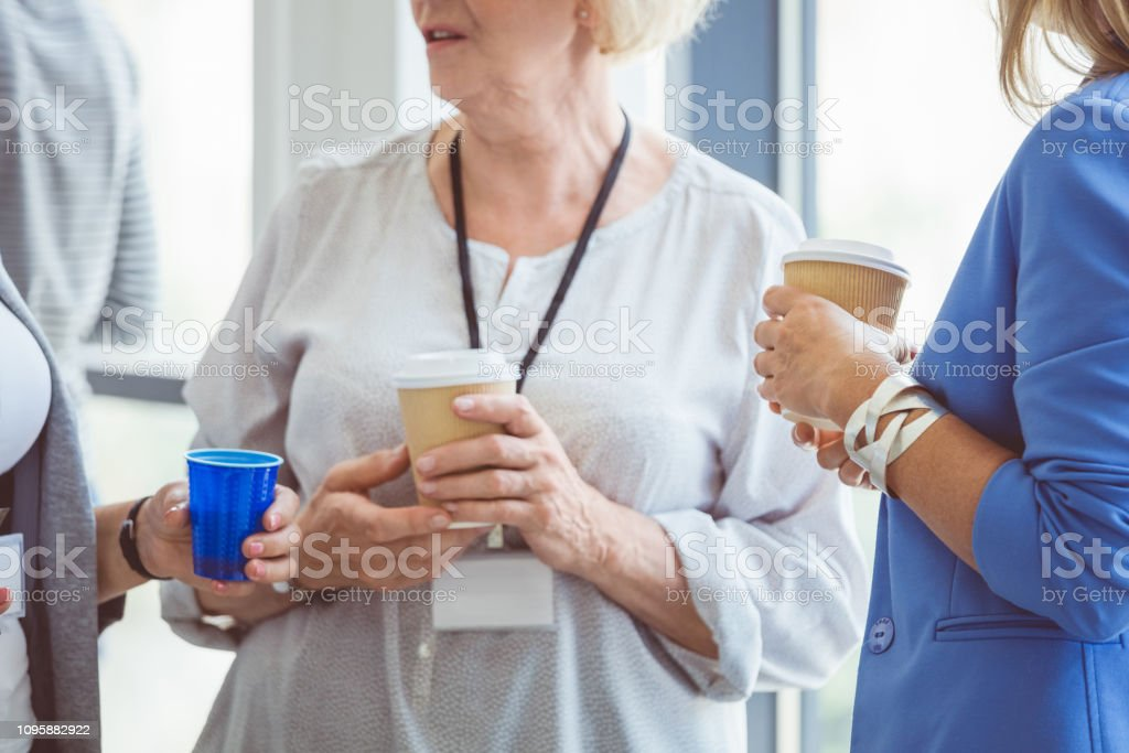 Coffee break during seminar Cropped shot of mature women holding a cup of coffee and talking during break. Coffee break during seminar. Adult Stock Photo