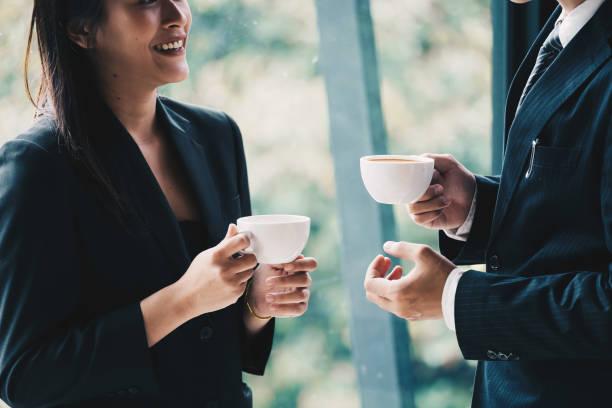 pausa para o café. executivos do grupo, estando no escritório moderno, prendendo uns copos, sorrindo que está no indicador - working in café - fotografias e filmes do acervo