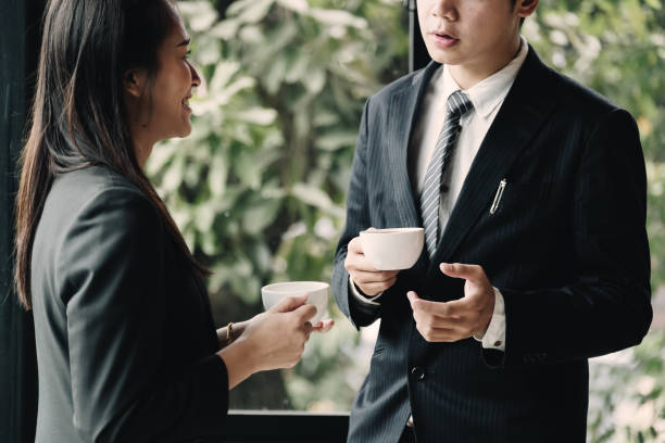 kaffeepause. Gruppen-Geschäftsleute, im modernen Büro stehend, mit tassen, lächelnd am Fenster stehend – Foto