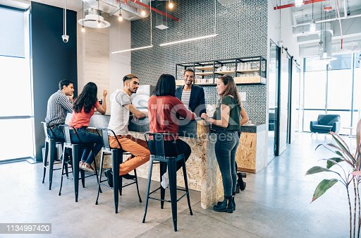 Business team during casual conversations at coffee break in co-working office