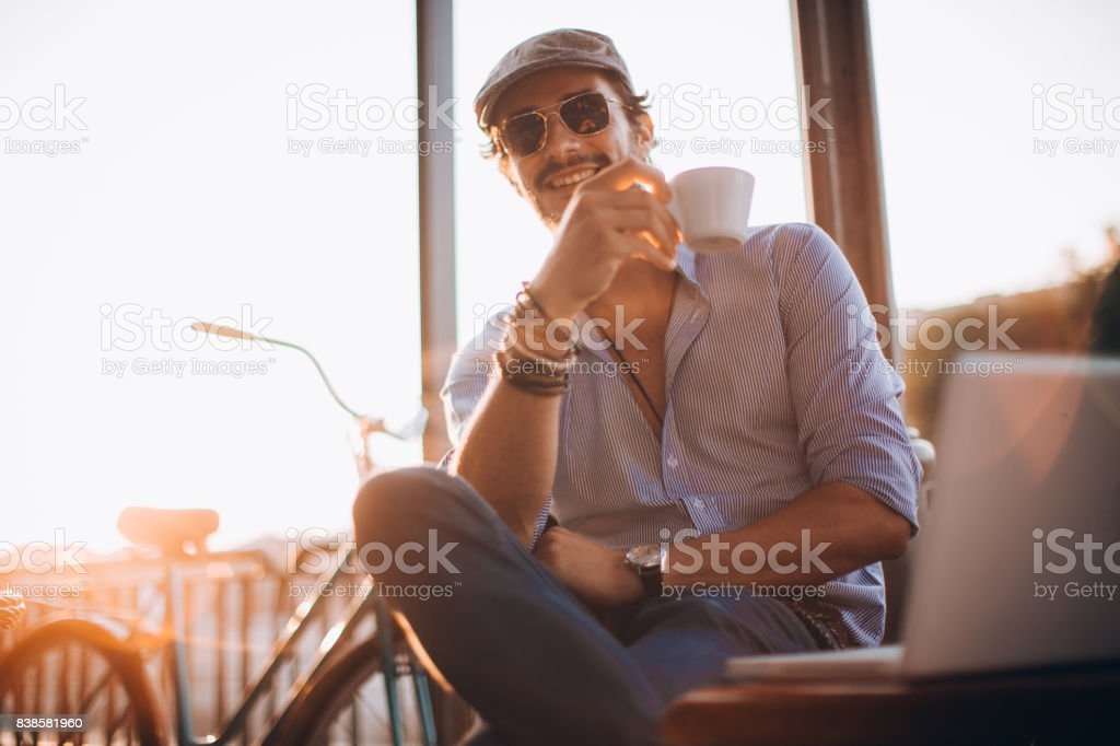 One man, modern and handsome, sitting in cafe outdoors, drinking...