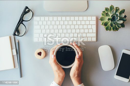 Coffeebreak at the workplace in the office, female hands holding mug with black coffee.