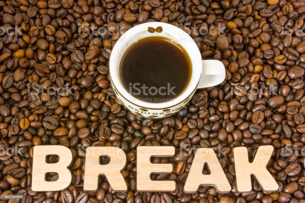 Coffee break photo. Cup with brewed coffee is on table, which filled with roasted coffee beans, next to word break. Idea to designate break for conferences, seminars, trainings and educational events stock photo