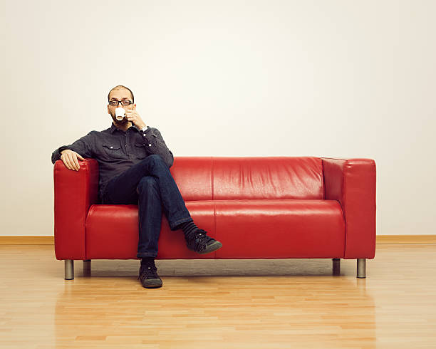 Coffee break Relaxed man having a coffee on a sofa. cross legged stock pictures, royalty-free photos & images