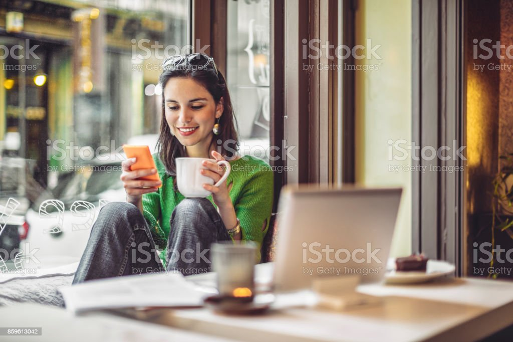 Coffee break Young woman enjoying a cup of coffee on a rainy day 20-29 Years Stock Photo