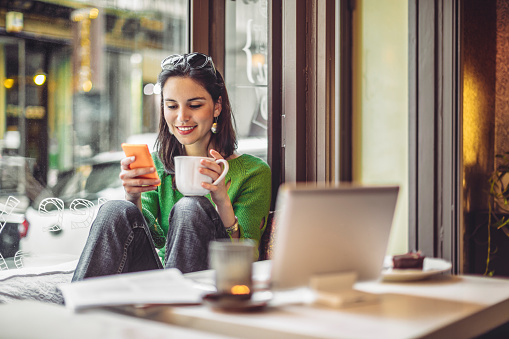 Young woman enjoying a cup of coffee on a rainy day