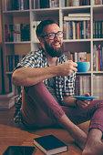 Joyful man sitting on the floor of his library, taking a coffee break