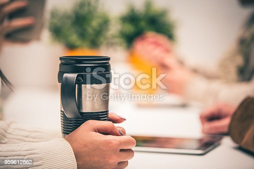 Close-up shot of female hands around travel mug placed on the office desk.