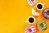 istock Coffee break with assorted donuts on yellow table with copy space. 821868974