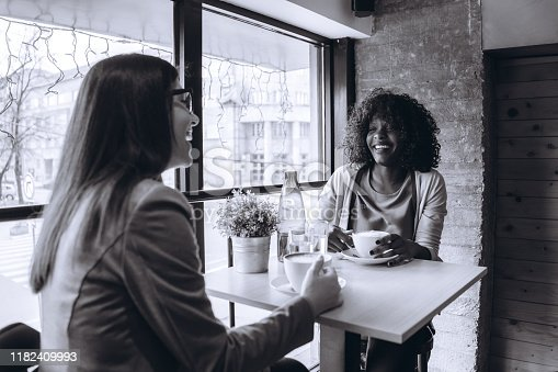 Two young multi-ethnic women drinking coffee in cafe.