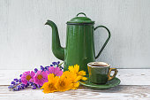 Vintage green coffee pot and cup of coffee and bouquet of wildflowers on white paint wooden background