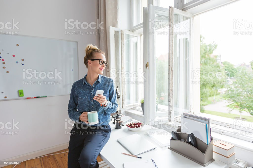 Coffee break, woman sitting on the desk, using smart phone Coffee break in an office. Woman wearing jeans shirt and nerd glasses holding a cup of coffee and using a smart phone, looking through the window. Adult Stock Photo