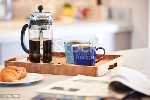 Coffee brewed in cafetiere on the kitchen work top with woman in background using sink