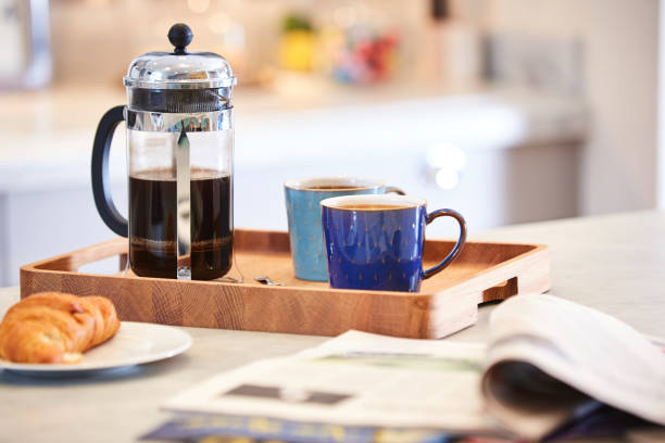 Coffee brewed in cafetiere on the kitchen work top Coffee brewed in cafetiere on the kitchen work top with woman in background using sink coffee pot stock pictures, royalty-free photos & images