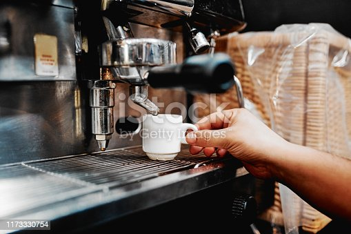 Shot of an unrecognizable barista operating a coffee machine inside a cafe