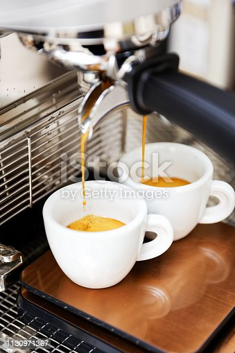 istock Coffee brewing in coffee machine. Espresso pouring in two cups. 1130971367