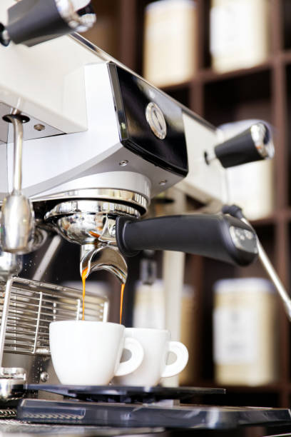 kaffeebrauen in kaffeemaschine. espresso gießt in zwei tassen. - mokkatassen stock-fotos und bilder