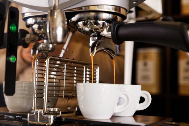 kaffeebrauen in kaffeemaschine. espresso gießt in zwei weißen tassen. flacher fokus. - mokkatassen stock-fotos und bilder