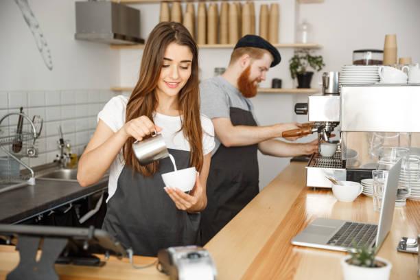 concepto de negocio café - barista cerca señora de delantal prepara y vierte leche en una taza caliente estando en el café. - barista fotografías e imágenes de stock