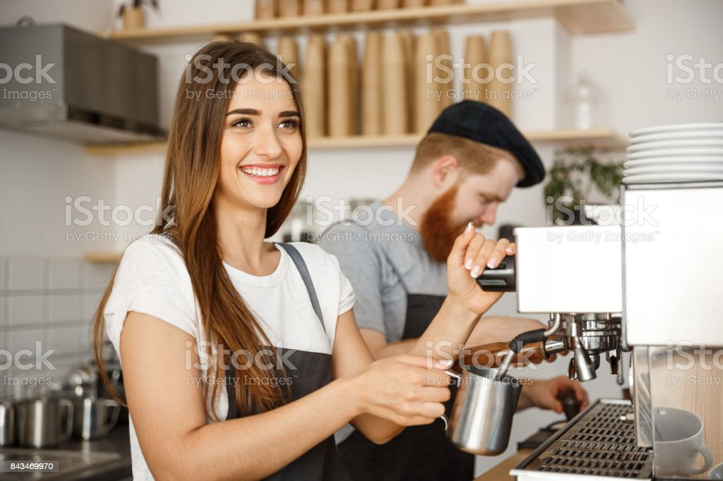 Coffee Business Concept - portrait of lady barista in apron preparing and steaming milk for coffee order with her partner while standing at cafe. stock photo