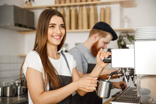 coffee business concept - portrait of lady barista in apron preparing and steaming milk for coffee order with her partner while standing at cafe. - barista stock photos and pictures