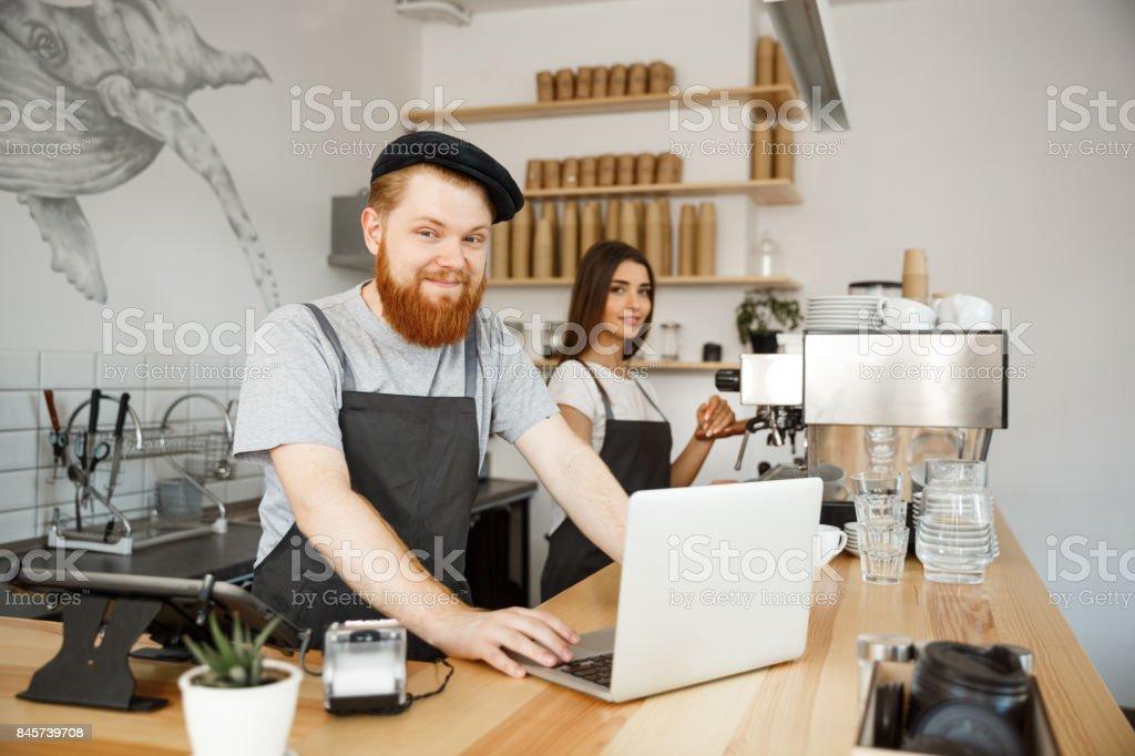 Kaffe affärsidé - ung stilig skäggig bartender, barista eller manager arbetar och hyvling i laptop på moderna kafé. bildbanksfoto