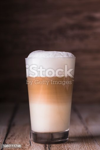 Coffee cafe latte macchiato in a high glass on a wooden background. There is copy space next to the glass, and the photo is horizontal.
