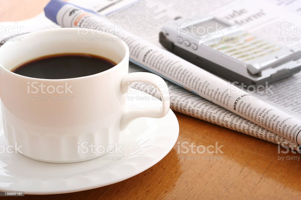 coffee, cellphone and newspaper on work table royalty-free stock photo