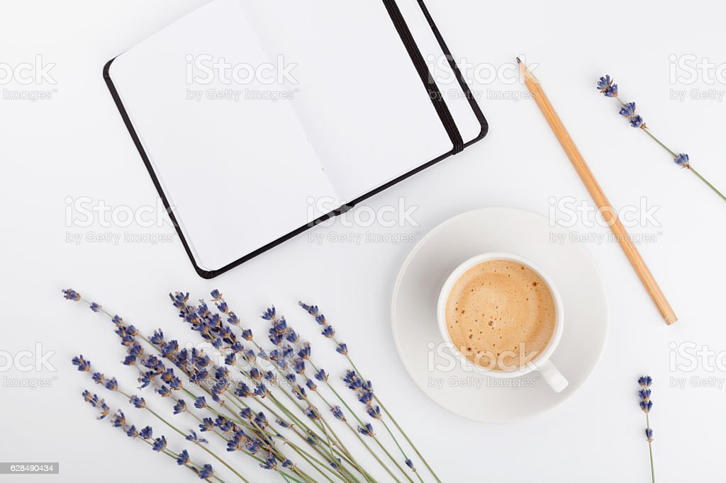 Coffee, clean notebook, lavender flower. Woman working desk. Flat lay. stock photo
