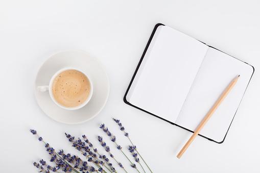 Coffee, clean notebook, lavender flower. Womans working desk. Flat lay.