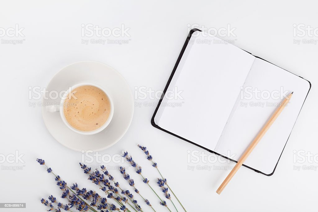 Coffee, clean notebook, lavender flower. Womans working desk. Flat lay. stock photo