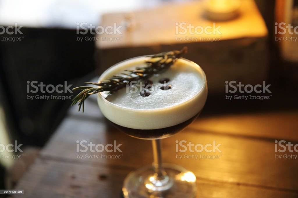 Coffee cocktail with coffee bean and rosemary on top with wood...
