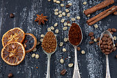 Coffee concept. Top view of three different varieties of coffee beans on dark vintage background. Three types of coffee on a spoon.