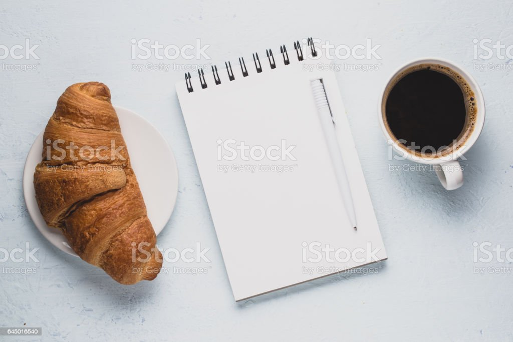 Coffee, croissant and a notepad on a light background. Breakfast concept stock photo