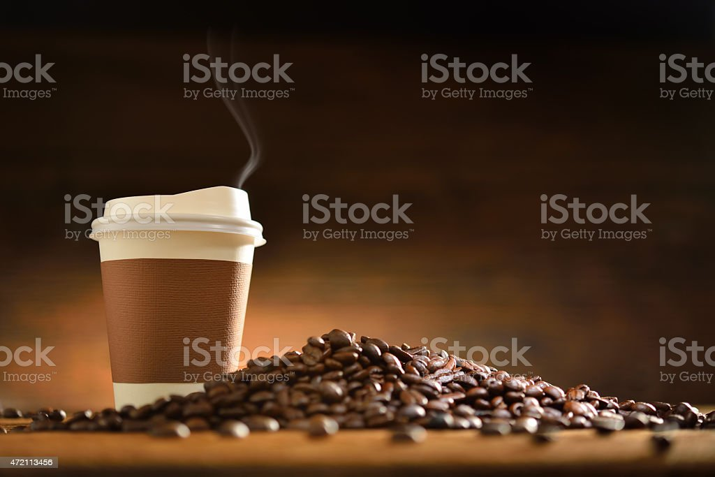Coffee cup and baked coffee beans pile on the desk stock photo