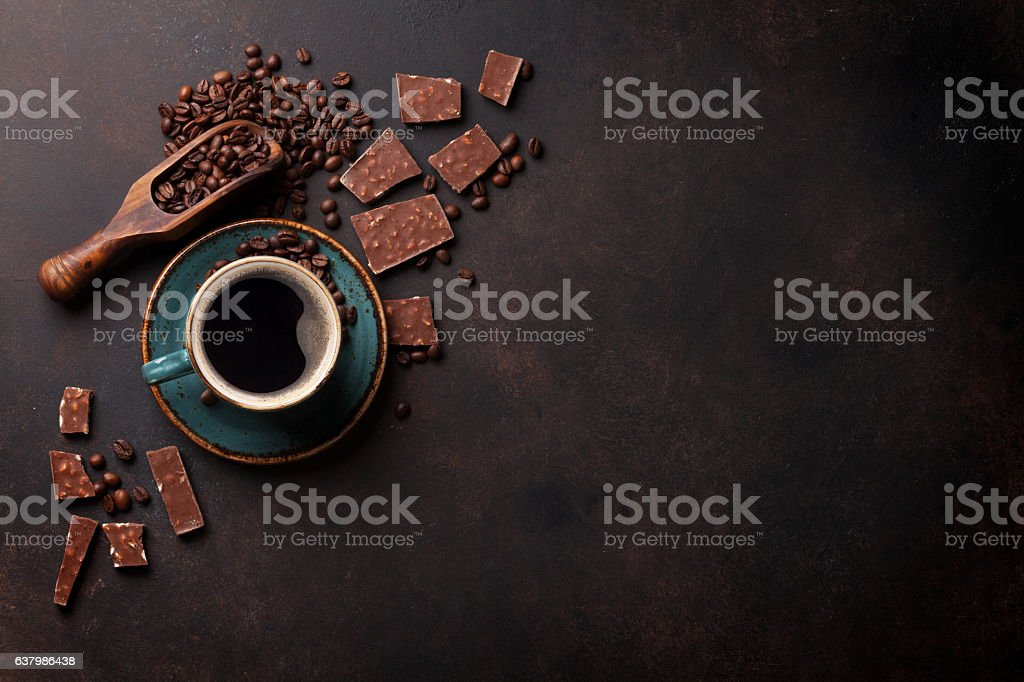 Coffee cup, beans and chocolate on old kitchen table. Top view with...