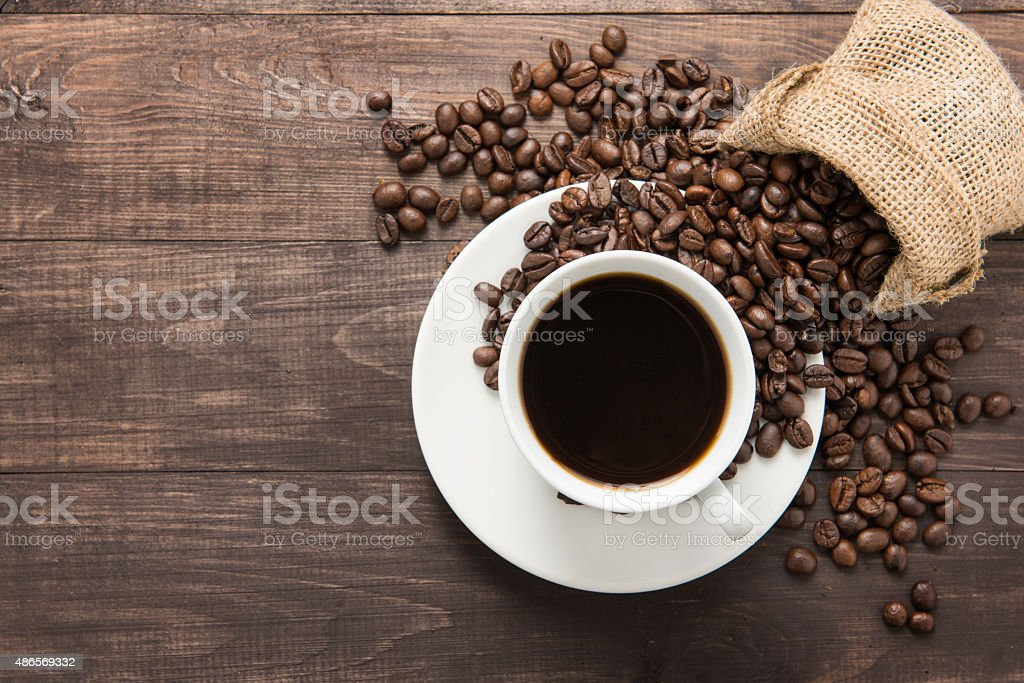Coffee cup and coffee beans on wooden background. Top view. stock photo