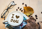 """Coffee cup and coffee beans on wooden table. Sign in foam says """"I Heart You"""""""