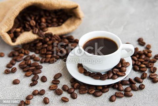 Cup of coffee with roasted beans on table